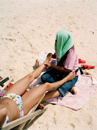 A Thai woman gives a foreign tourist a massage during the mid-day heat.